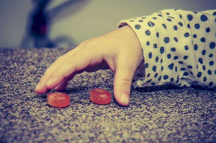 Hand eines Kindes greift nach zwei Bonbons